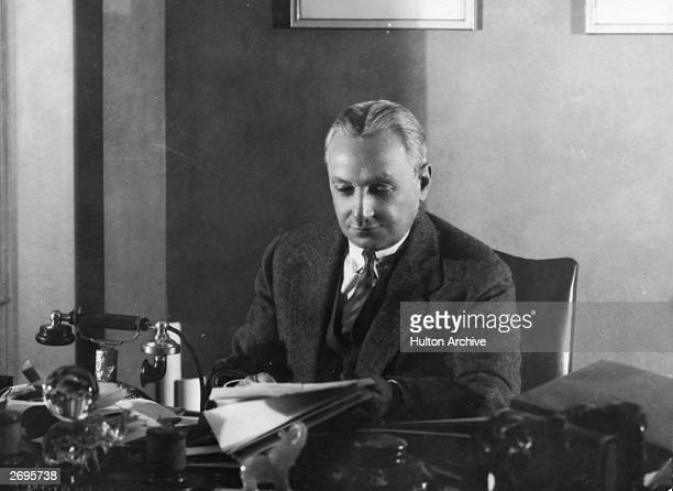 American theater producer Florenz Ziegfeld Jr reads while sitting behind a cluttered desk