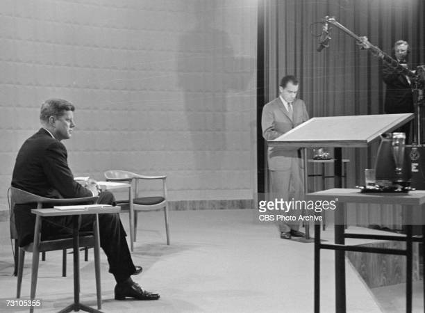 American then-senator and future President John F. Kennedy sits at left and then-Vice President and future President Richard Nixon stands, as both...