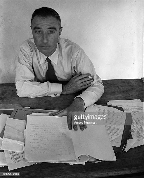 American theoretical physicist Dr J Robert Oppenheimer as he sits at a table covered in papers Berkeley California June 6 1948