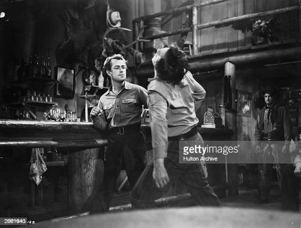 American tough guy actor Alan Ladd lays his opponent out cold in a barroom brawl scene from the film 'Shane' directed by George Stevens for Paramount