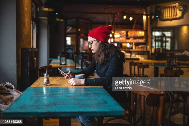 american tourist chatting on her smartphone while sitting at a cafe - candid forum stock pictures, royalty-free photos & images