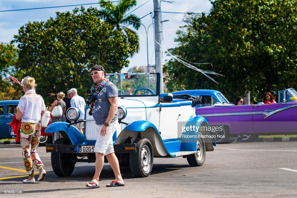 American tourists getting off an old convertible car in the ...