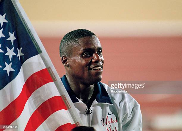 American track and field athlete Carl Lewis carries the national flag in celebration after finishing in first place to win the gold medal in the...