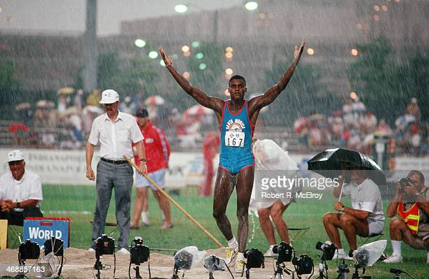 American track and field athlete Carl Lewis raises his arms in the rain on the field of IndianaPurdue University Stadium during at the US Olympic...