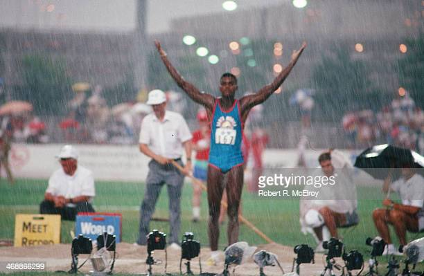 American track and field athlete Carl Lewis raises his arms in the rain on the field of Indiana-Purdue University Stadium during at the US Olympic...