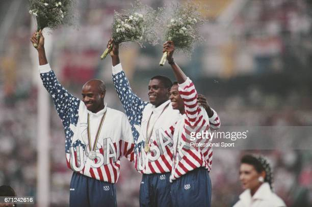 American track and field athletes from left silver medallist Mike Powell gold medallist Carl Lewis and bronze medallist Joe Greene of the United...
