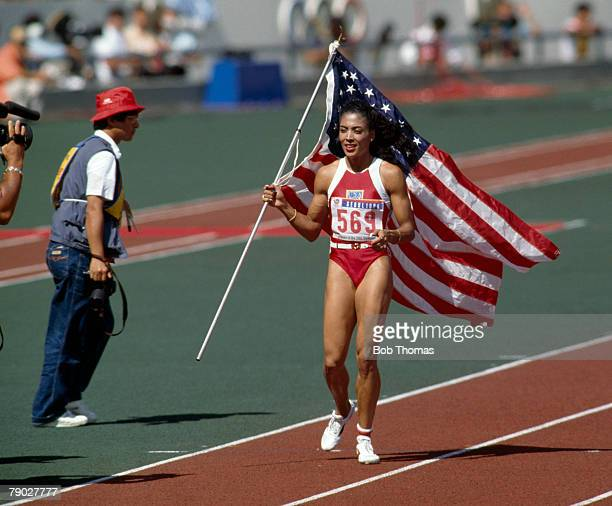 American track athlete Florence Griffith Joyner celebrates with her country's flag after finishing first to win the gold medal in the final of the...