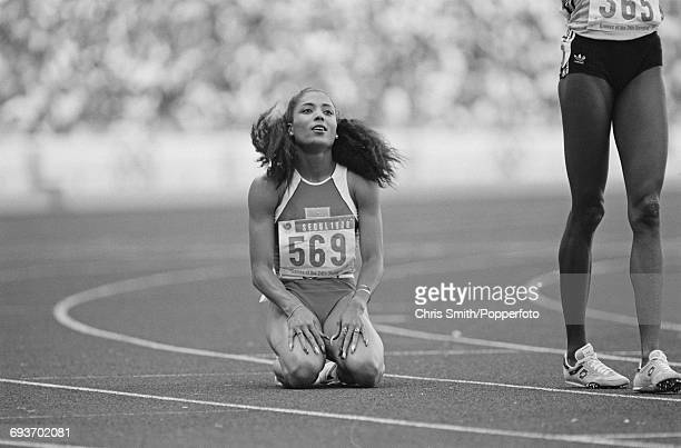 American track athlete Florence Griffith Joyner sinks to her knees on the track after crossing the finish line in first place to win the gold medal...