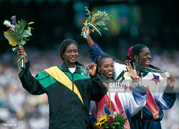 American track athlete Gail Devers stands in centre on the podium after finishing in first place to win the gold medal in the final of the Women's...