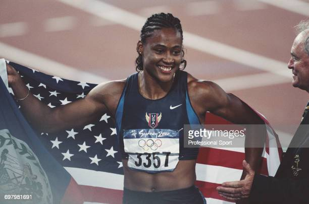 American track athlete Marion Jones pictured holding the stars and stripes national flag after finishing in first place to win the gold medal for the...