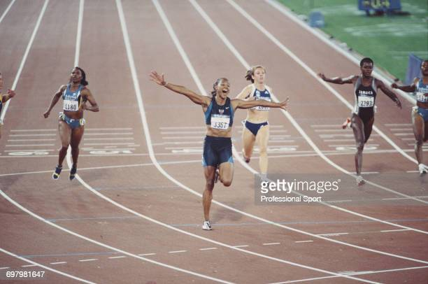 American track athlete Marion Jones raises her arms in the air in celebration after crossing the finish line in first place to win the gold medal for...