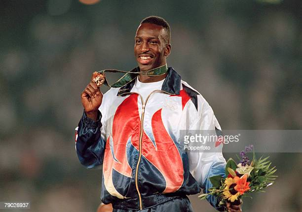 American track athlete Michael Johnson celebrates on the medal podium after finishing in first place in a new world record time to win the gold medal...