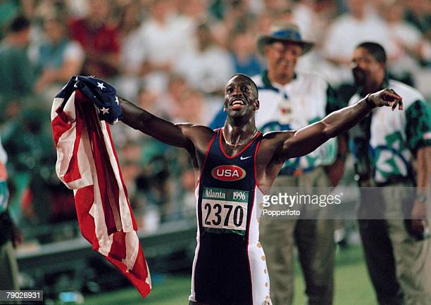 American track athlete Michael Johnson celebrates with the United States national flag after finishing in first place in a new world record time to...