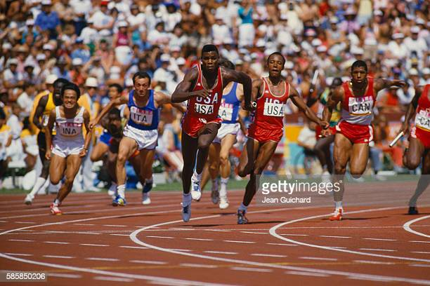 American track star Carl Lewis takes the baton from Calvin Smith during the final race in the Men's 100meter relay at the 1984 Summer Olympic Games