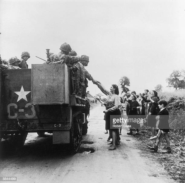 American troops advancing through France are greeted by civilians near the village of Notre Dame de Cenily, August 1944.