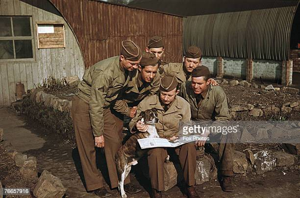 American troops and a pet dog looking at a scrapbook during training in Northern Ireland March 1942