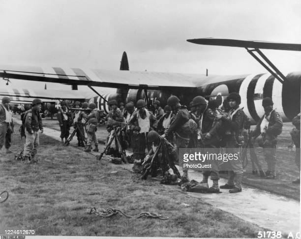 American troops from the 82nd Airborne Division check their equipment before the first airborne assault on the continent, England, June 6, 1944. A...