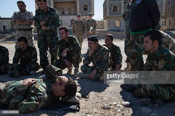 """American troops look on as Kurdish Peshmerga fighters assist """"wounded"""" comrades during medical training on November 3, 2015 in Erbil, Iraq. The..."""