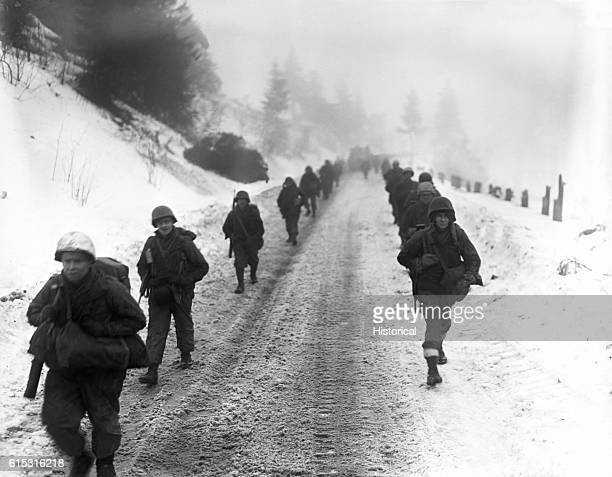 American troops of the 1st Division march through snow towards Murringen Belgium on January 31 during the Battle of the Bulge | Location near...