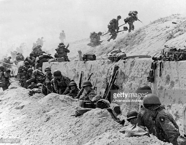 American troops of the 4th Infantry Division at Utah Beach taking a breather before continuing the assault over the hill to the interior of France...