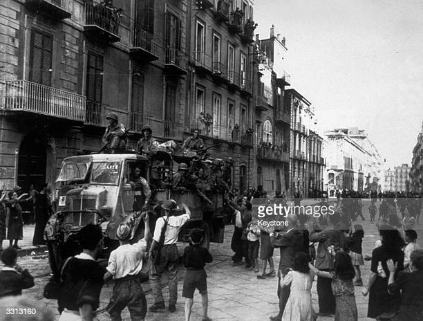 American troops travelling through Naples in British trucks on their way to the front are given a warm welcome by the Neapolitans.