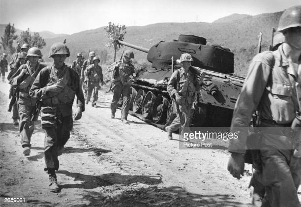 American troops walking down a road in Korea. Original Publication: Picture Post - 5086 - We Follow The Road To Hell - pub. 1950