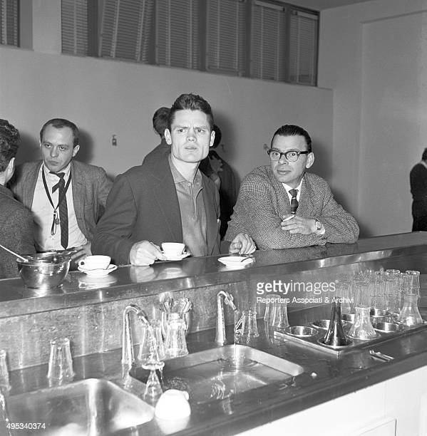 American trumpet player Chet Baker leaning with a coffee cup on the couter of the cafà© of the recording label Rca with other unidentified men 1961