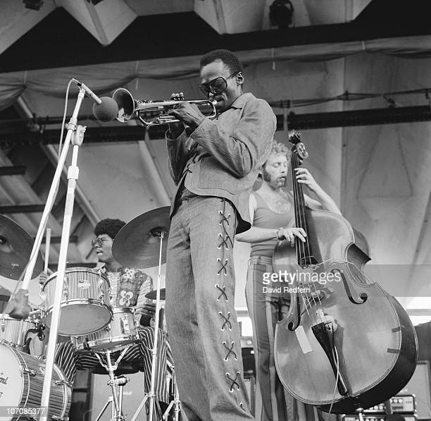American trumpeter and composer Miles Davis performing at the Newport Jazz Festival at Newport, Rhode Island, 5th July 1969. Behind Davis are Jack...