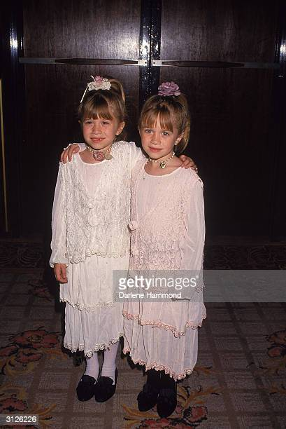 American twin child actors Mary Kate and Ashley Olsen stand arminarm at an event early 1990s