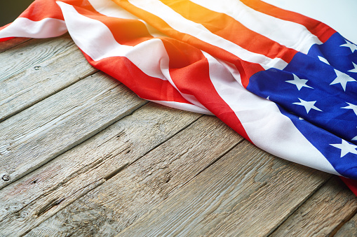 American USA flag freely lying on the textured wooden background. News template about the America. Copy space. 1255022012