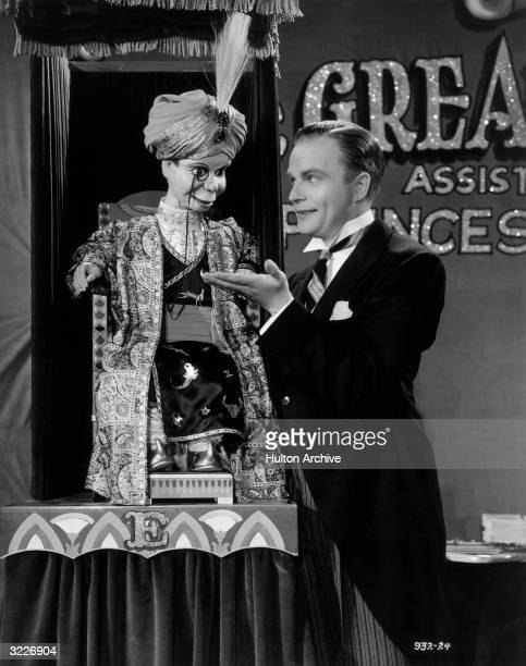 American ventriloquist Edgar Bergen dressed in tails and standing with his palm outstretched to his dummy Charlie McCarthy who is dressed as a...