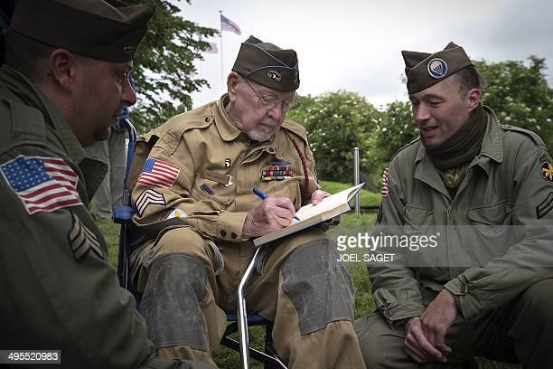 American veteran Donald Burgett signs a book for two men dressed as a World War II-era American soldiers in Saint-Come-du-Mont, near Utah beach, on...