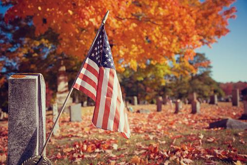 American veteran flag in autumn cemetery 615743990