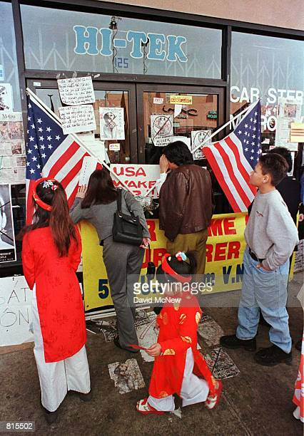 American Vietnamese demonstrators peer into Truong Van Tran's shop February 16 in the Little Saigon area of Westminster California to see where Tran...