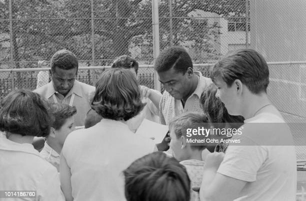 American vocal group the Four Tops signing autographs at a sports event in New York City 1965