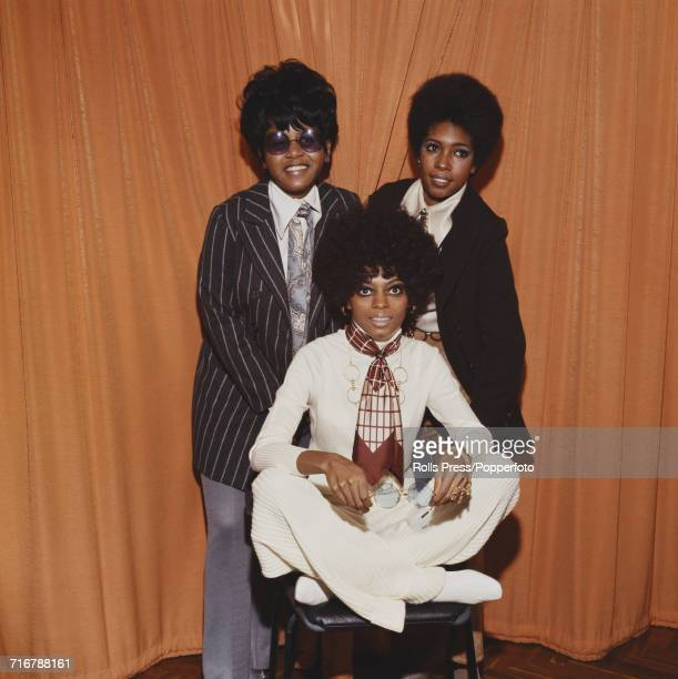 American vocal group The Supremes featuring Diana Ross seated wearing a neck scarf and holding a pair of metal rimmed sunglasses with behind Cindy...