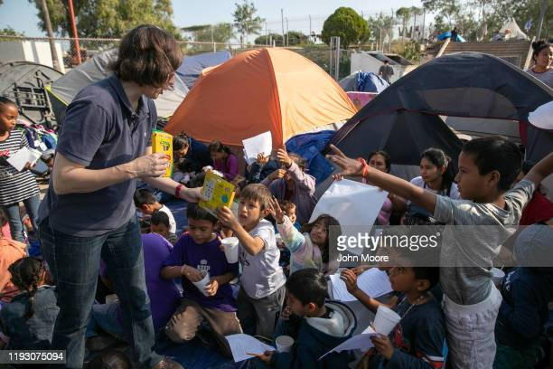American volunteer Mary Keenan hands out markers during class at The Sidewalk School for immigrant children at a squalid Remain in Mexico camp for...