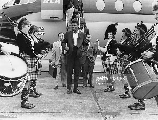 American WBC world heavyweight boxing champion Muhammad Ali is greeted by a traditional Scottish pipe band on his arrival at Glasgow Airport 18th...