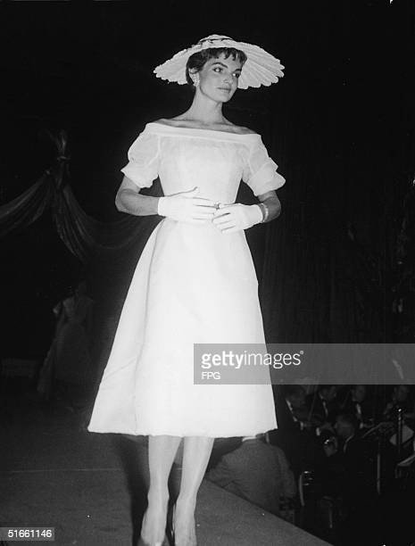 American wife Jacqueline Kennedy walks the catwalk as she models a French designer dress, gloves, and hat at the annual 'April in Paris' ball where...