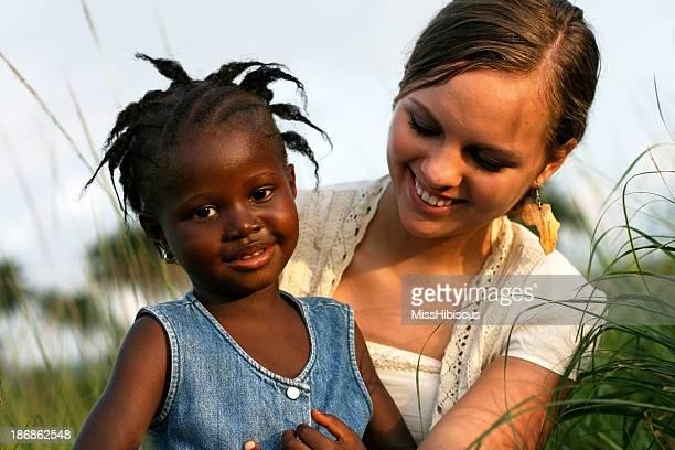 Amerikanische Frau hält Afrikanische Mädchen
