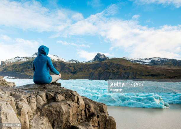 american woman looking at scenic view of glacier lagoon in iceland - glacier lagoon stock photos and pictures