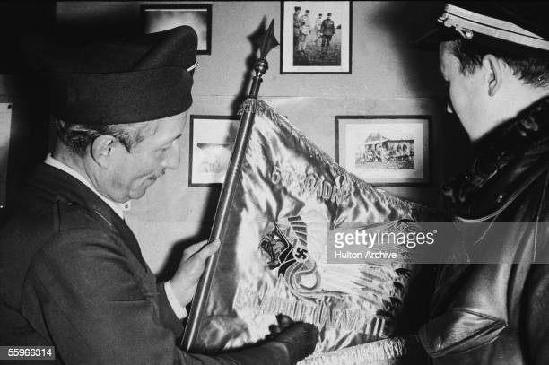 American World War I veteran Clifford de Roode presents a French fighter pilot with a Lafayette Escadrille flag featuring an American Indian...