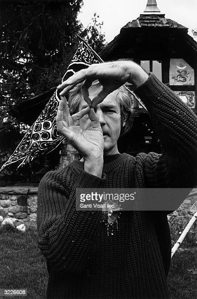 American writer and activist Timothy Leary holding his fingers in a chanting position while standing outdoors on his farm in Millbrook New York
