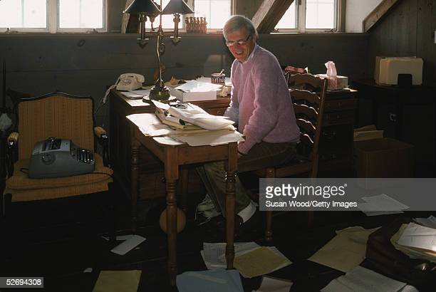 American writer and journalist George Plimpton sits at a desk strewn with papers in his writing studio at his summer home, Wainscott, New York,...