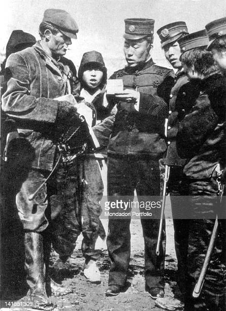 American writer and journalist Jack London showing his pass to some Japanese soldiers At the time he was special correspondent for the media company...