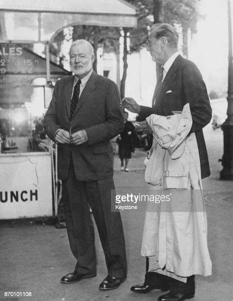 American writer Ernest Hemingway and actor Gary Cooper leave a cinema on the Rue Royale in Paris, France, 14th September 1956. They had met...