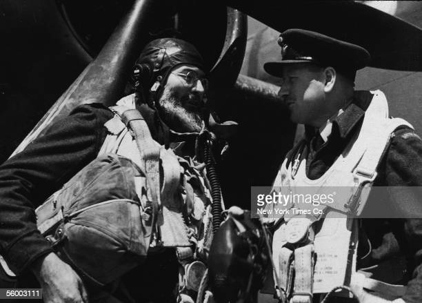 American writer Ernest Hemingway and British Royal Air Force Wing Commander L.A. Lynn, both dressed in protective clothing and holding supplies,...