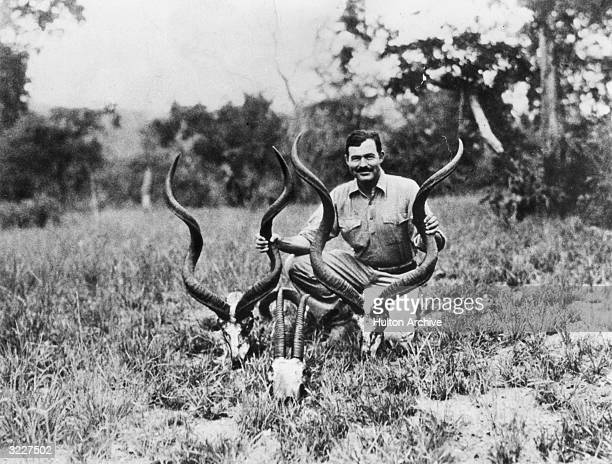 American writer Ernest Hemingway kneels while holding a pair of antelope horns during a safari, Africa.