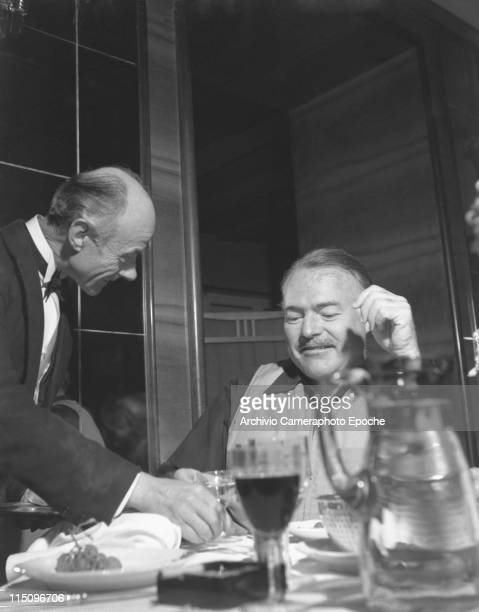 American writer Ernest Hemingway sitting at a restaurant table wearing a hunter waistcoat a waiter wearing a tailcoat and a bow tie serving him a...