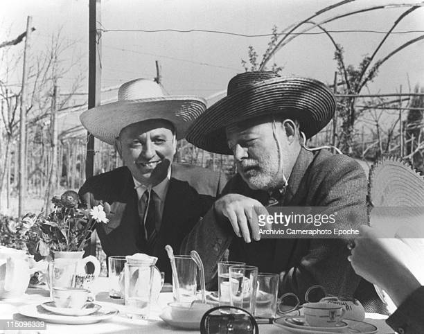 American writer Ernest Hemingway sitting at a table with Giuseppe Cipriani both wearing a sombrero straw hat glasses cups and flowers on the table...
